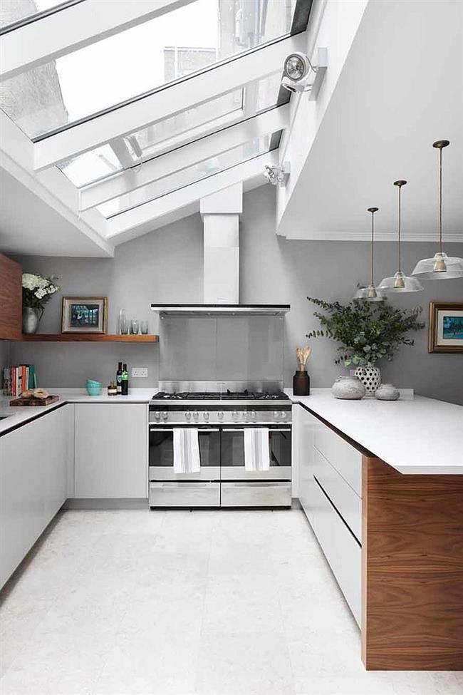 Небольшая кухня с мансардными окнами в скошенном потолке.