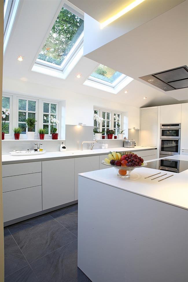 Кухня в белых тонах с прямоугольными мансардными окнами.