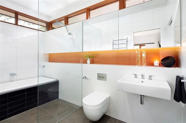 Черно-белая ванная с элементами оранжевого цвета.