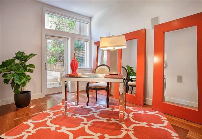 Стильный офис с оранжевым ковром и рамами для зеркал.
