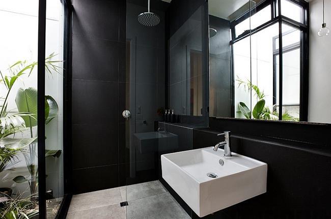 Ванная комната черного цвета с живыми растениями.