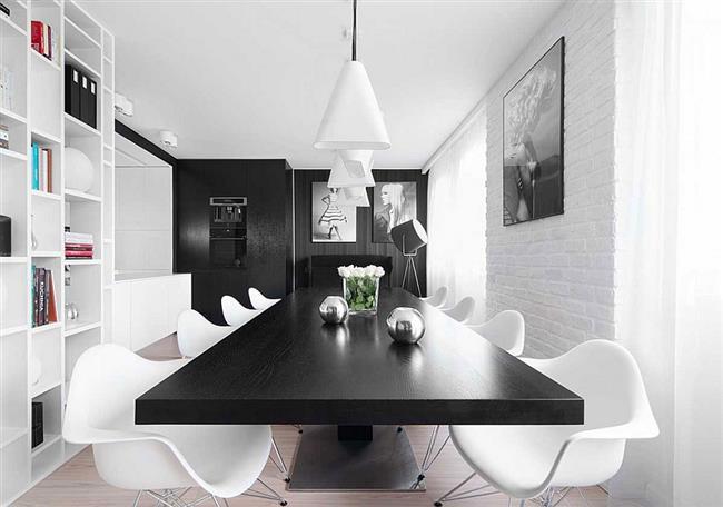 Элегантная столовая польской квартиры в черных и белых цветах.