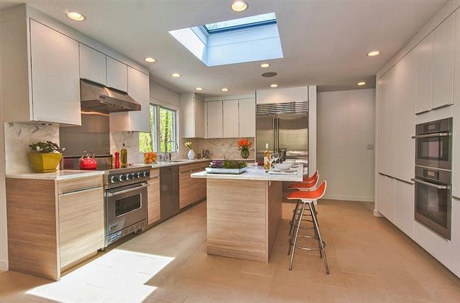 Небольшая кухня с оранжевыми аксессуарами и мансардным окном.