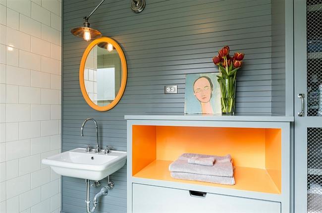 Маленькая ванная с аксессуарами оранжевого цвета.
