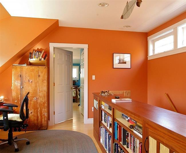 Яркие оранжевые стены в деревенском домашнем офисе.