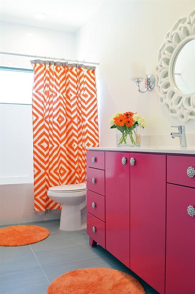 Ванная комната с аксессуарами яркого оранжевого и розового цветов.