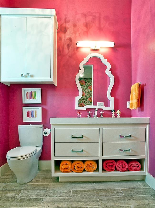 Стильная ванная с яркими розовыми стенами.