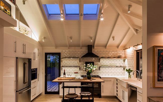 Столовая-кухня с мансардными окнами и подвесными светильниками.