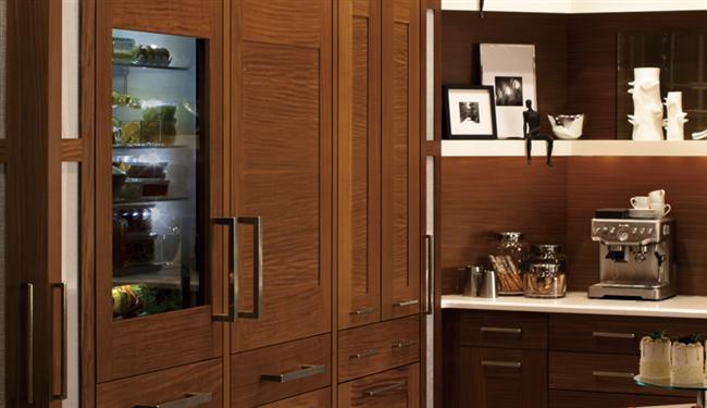 Небольшой холодильник, встроенный в кухонный шкаф.