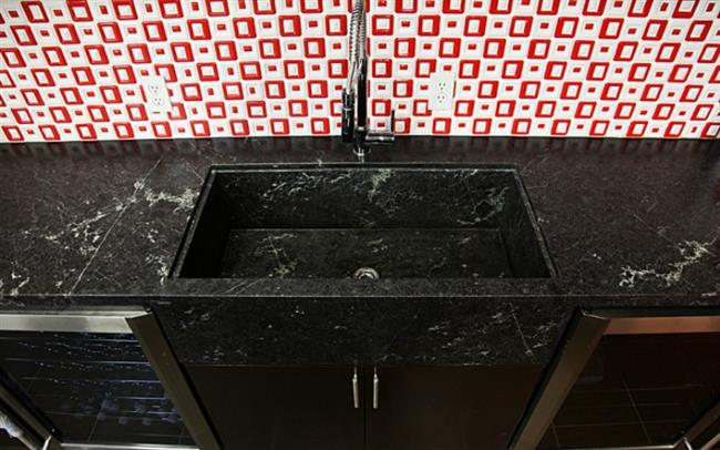 Стильная кухонная мойка из черного гранита с полосами.