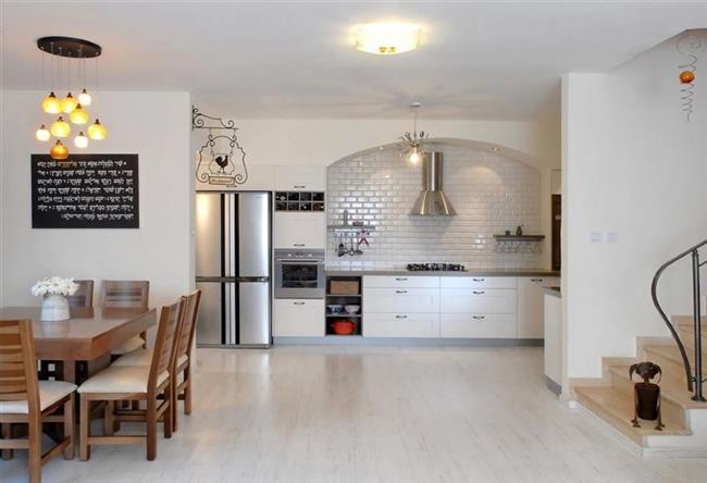 Минималистическая кухня-столовая с белым ламинатом.