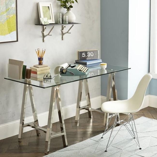Современный металлический стол со стеклом в интерьере просторной спальни.