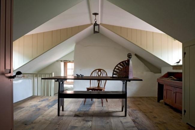 Деревянный письменный стол в мансардном помещении.