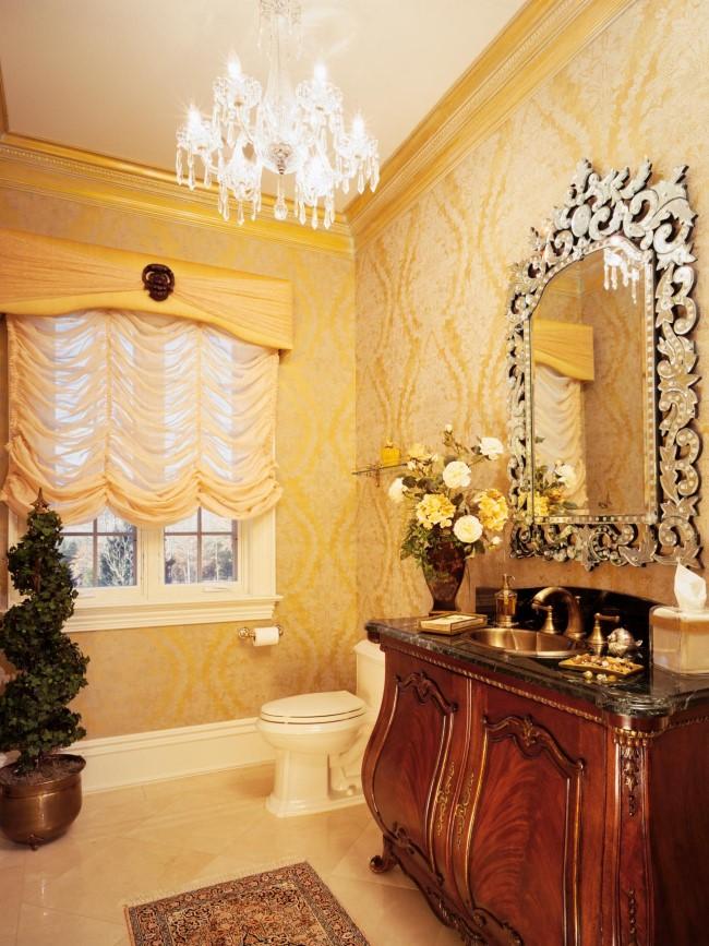 Хрустальная люстра в небольшой желтой ванной комнате.