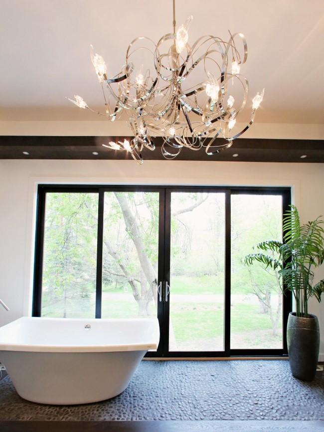 Черно-белая ванная с абстрактной люстрой.