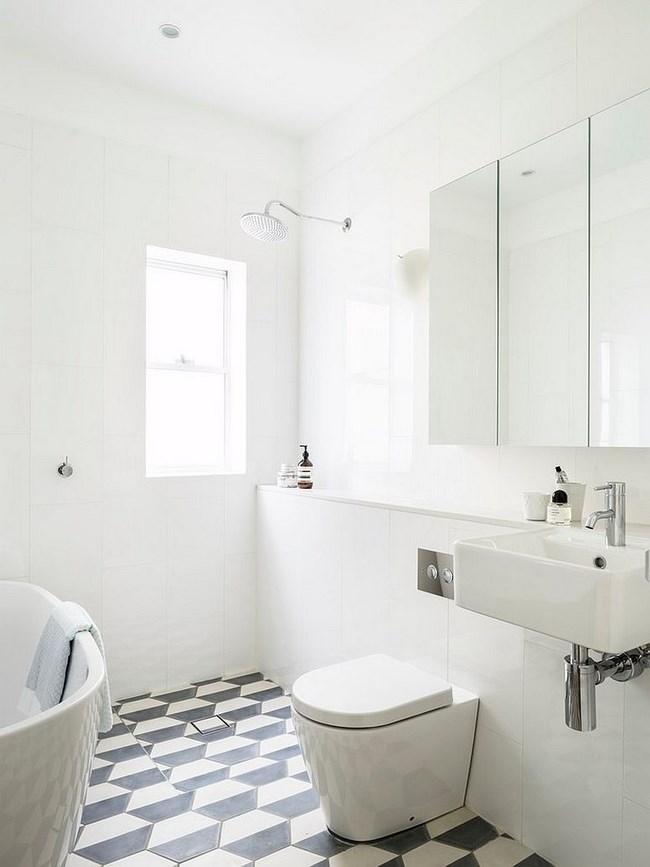 Черно-белое напольное покрытие в белой ванной.