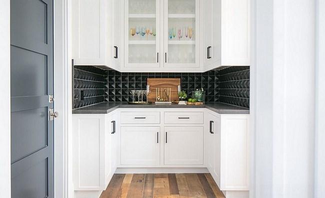 Черная геометрическая плитка в белой кухне.