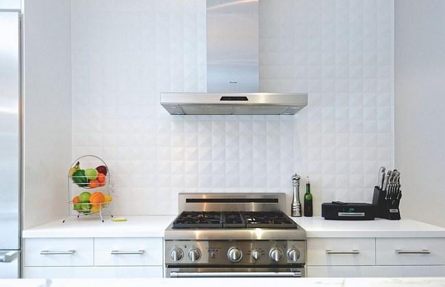 Белая геометрическая плитка на стенах современной кухни.
