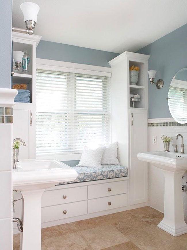 Ванная комната с окном и белой встроенной мебелью.