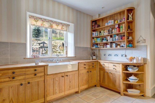 Полосатые обои и плитка в небольшой кухне.