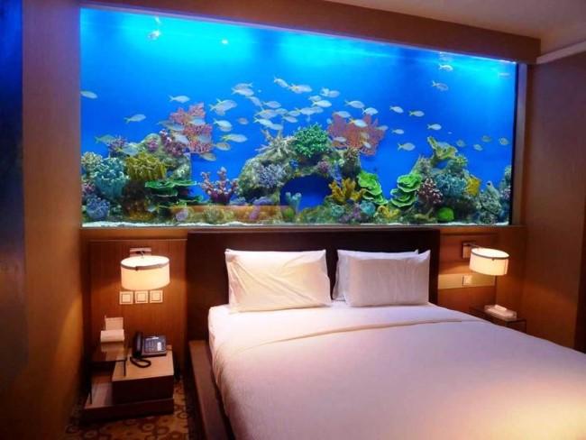 Просторный стильный аквариум у основания кровати в спальне.