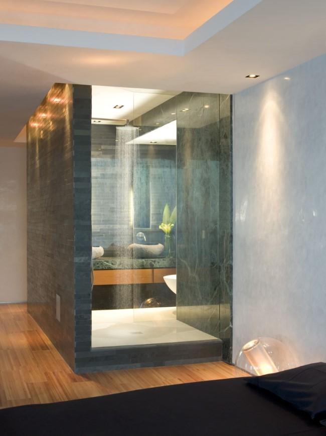 Душевая кабина из мрамора в интерьере современной спальни.