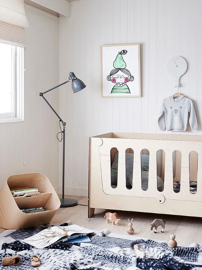 Скандинавская детская комната с деревянной кроваткой и детскими игрушками.
