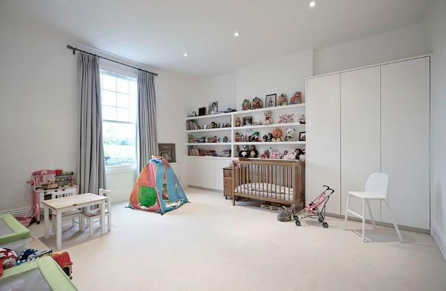 Просторная светло-серая детская с белоснежной мебелью и яркими игрушками.