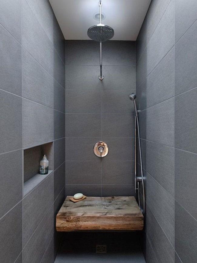Узкая душевая кабинка со стенами, выложенными каменными плитами.