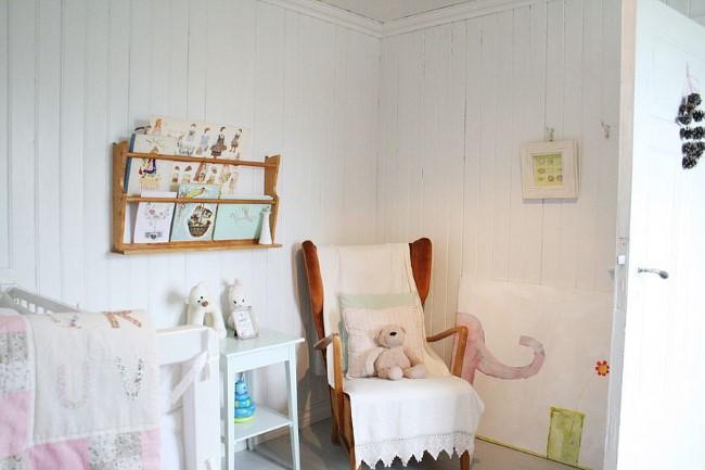 Детская комната загородного дома с деревянными белыми стенами.