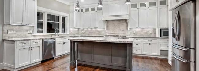 Столешница из белого гранита в белой современной кухне.