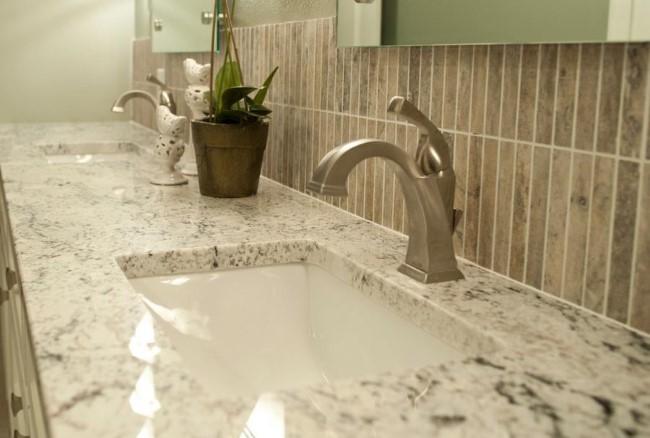 Раковина в ванной комнате, декорированная белым гранитом.