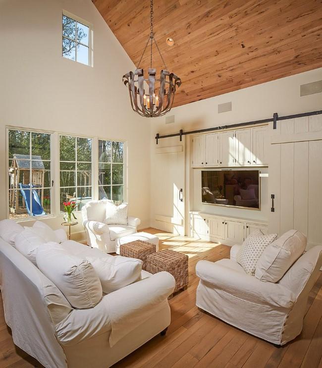 Раздвижные двери для изоляции телевизора в белой гостиной.