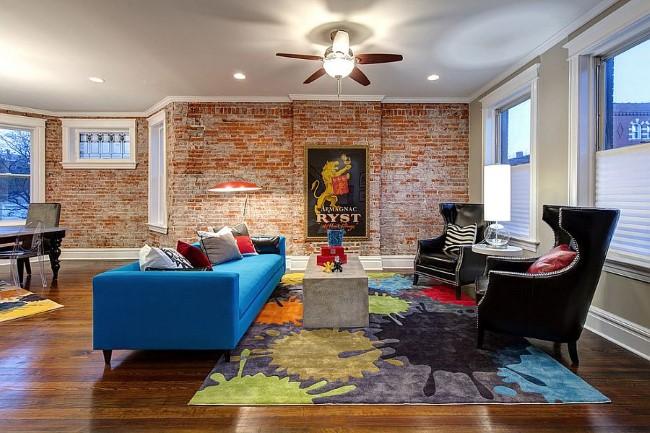 Кирпичная кладка с яркой картиной в интерьере просторной гостиной.