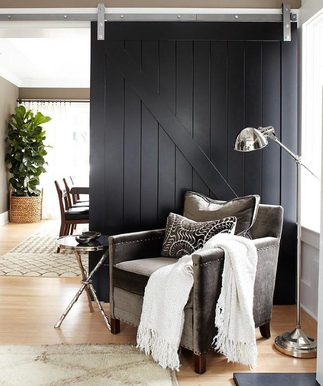 Раздвижные темно-серые двери в небольшой гостиной.