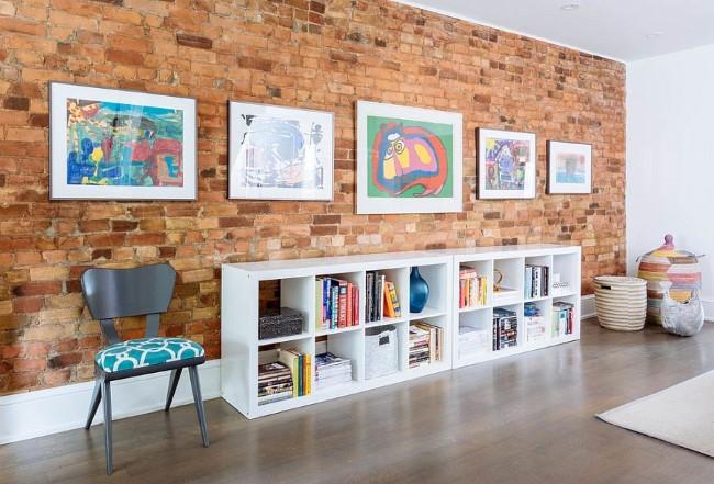Современные картины и напольный книжный шкаф на фоне кирпичной кладки.