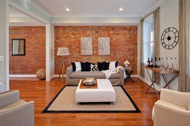 Кирпичная кладка и белые крашенные стены в просторной гостиной.