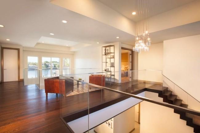 Уникальная хрустальная люстра и встроенные светильники в интерьере гостиной.