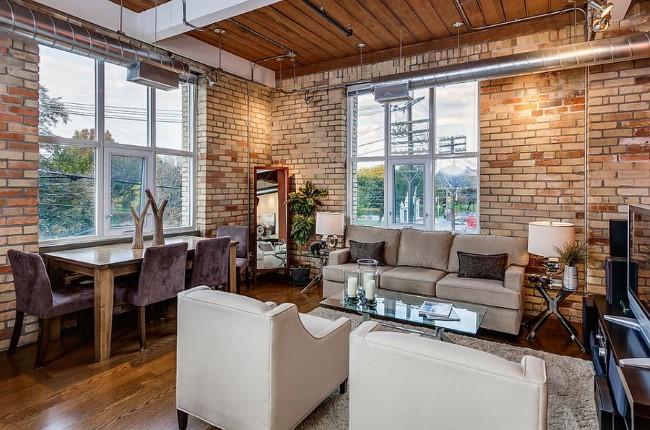Стильная индустриальная гостиная с кирпичными стенами.