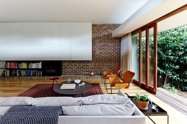 Кирпичная стена в интерьере современной гостиной с открытой планировкой.