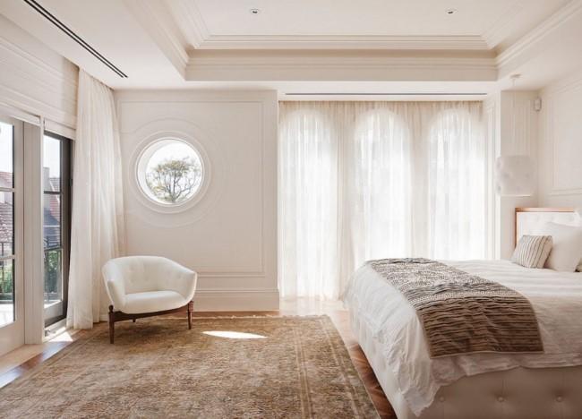 Белый подвесной потолок, белые стены и мебель в интерьере стильной спальни.
