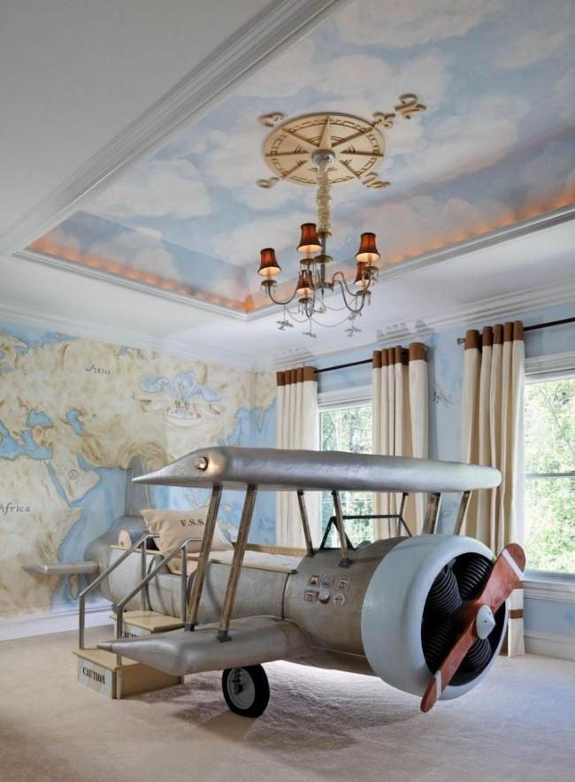 Подвесной потолок с рисунками и узорчатая люстра в интерьере детской.