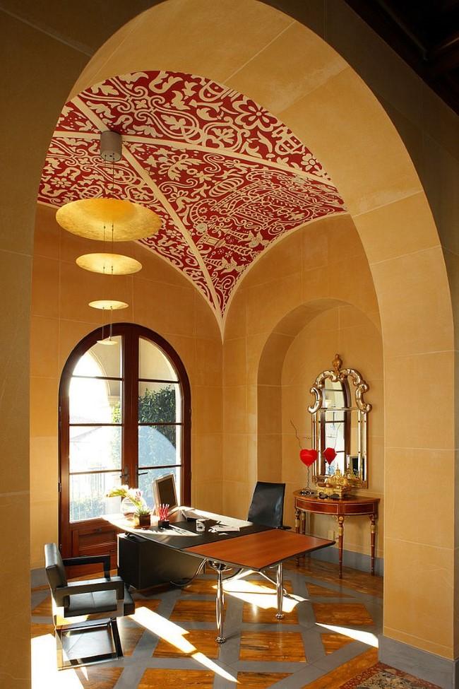 Яркие красно-белые узорчатые обои на потолке домашнего кабинета.