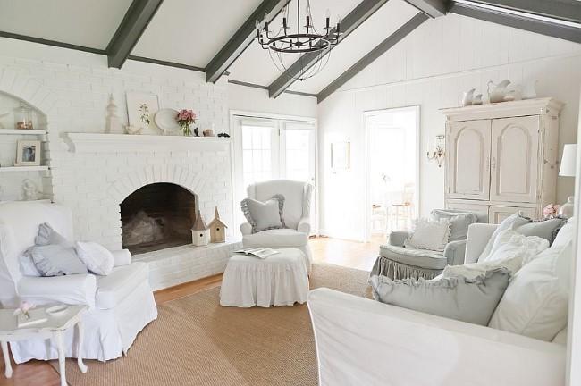Шебби шик гостиная с белой мягкой мебелью и камином.