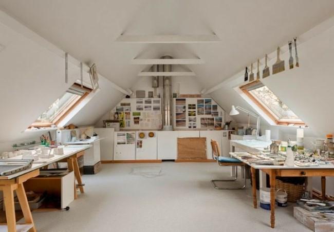 Просторная белая студия с деревянной мебелью на чердаке двухэтажного частного дома.