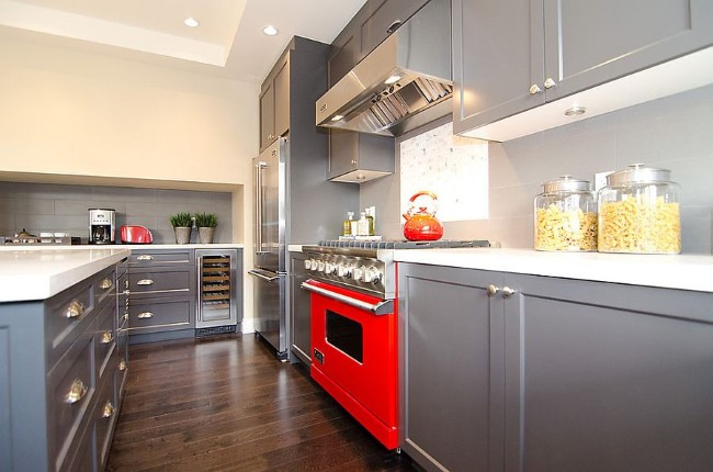 Элегантная кухня серого цвета с аксессуарами и техникой в красных тонах.