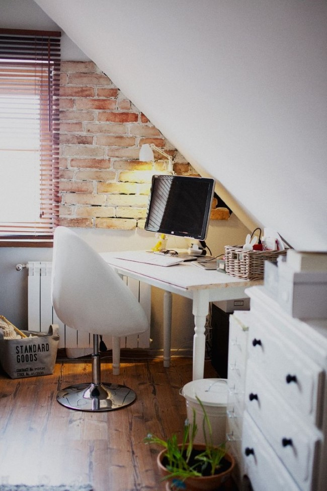 Маленький домашний кабинет в мансарде с белой мебелью и кирпичной стеной.