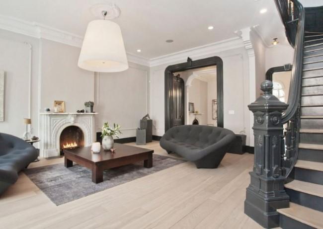 Темно-серый и белый тона в интерьере просторной гостиной с камином.