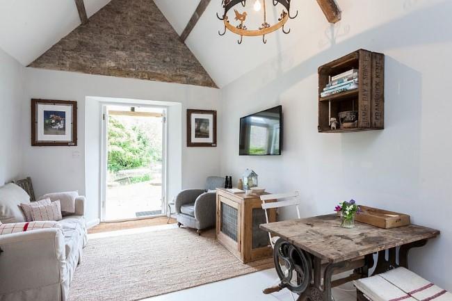 Белоснежные стены и предметы мебели из натурального дерева в гостиной шебби шик.