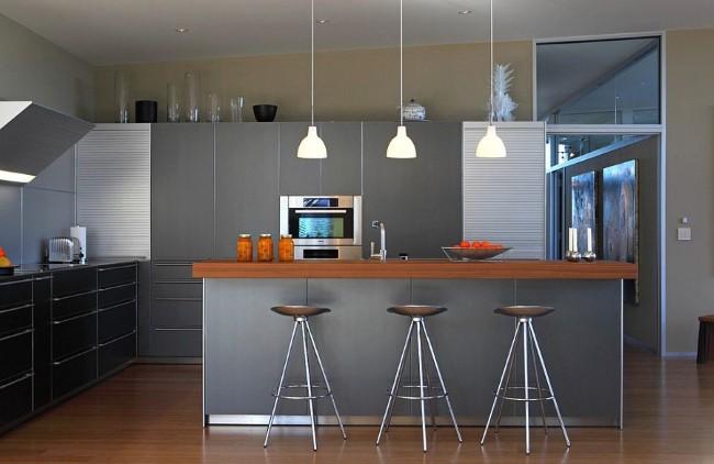 Многофункциональная кухня с серой мебелью и барной стойкой.
